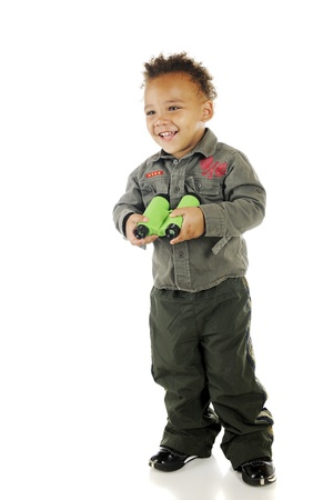 An adorable preschooler wearing Air Foce garb happily holding a pair of binoculars   On a white background Stock Photo - 14668973