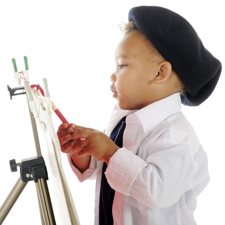 Closeup image of an adorable preschool artist painting on an easel in his smock and French baret   On a white background  photo