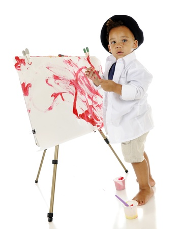 An adorable preschooler looking back at the viewer as he creates his own painted masterpiece   He Stock Photo