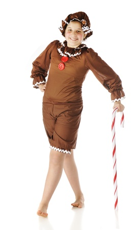 rick rack: A cute preteen gingerbread girl leaning on a giant candy cane   Isolated on white  Stock Photo