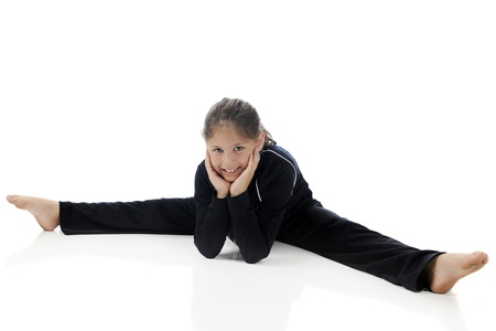 A pretty elementary girl doing the splits in her gymnastics warm-up suit   On a white background  Zdjęcie Seryjne