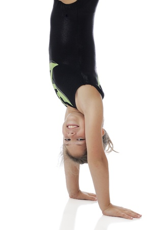 A happy elementary girl doing a handstand in her gymnastics leotards   On a white background  photo