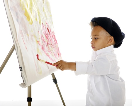 An adorable preschool artist painting on an easel while wearing a white smock and black French beret   On a white background  photo