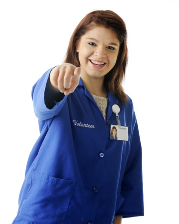 smock: A delighted young teen pointing directly at the viewer in her volunteer smock and ID tag.  Focus on girls eyes.  On a white background. Stock Photo