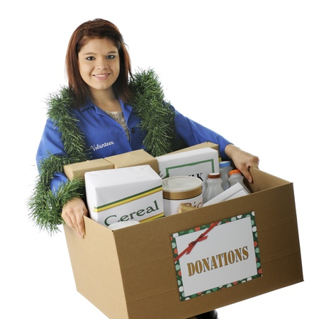 An attractive young volunteer holding a large box of food donated for the holidays.  On a white background. photo