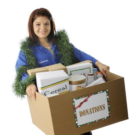 Een aantrekkelijke jonge vrijwilliger met een grote doos van voedsel gedoneerd voor de feestdagen. Op een witte achtergrond.