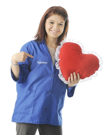 A happy teen volunteer holding a heart-shaped pillow while pointing to the word volunteer on her volunteer smock.  On a white background.