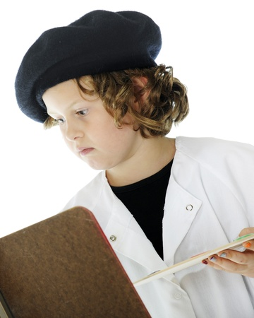 smock: Close-up portrait of a serious elmentary-aged artist at work in her smock and black beret   On a white background