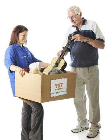 A young teen holding a large box with a holiday  Toy Donations  sign as an elderly man is donating a toy guitar   Focus on girl,  On a white background Stock Photo - 14826484