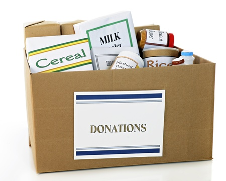 A corrugated carboard box with a  Donations  sign on it and filled with a variety of food for the needy   On a white background