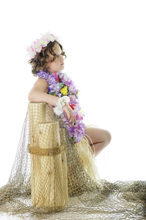 leis: A contemplating elementary hula girl leaning against net covered pier posts   On a white background  Stock Photo