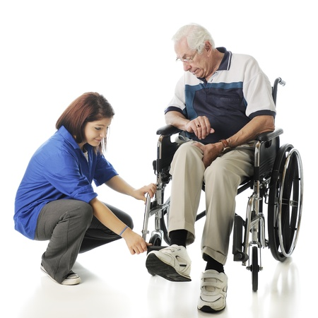 An attractive young teen adjusting the foot pedals on an elderly man