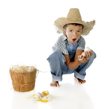 An adorable preschool farm-boy exclaiming over the eggs he dropped   On a white background
