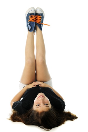 A pretty preteen looking back over her head at the viewer as she lays in her back, legs straight up in the air to show off her blue sneakers with bright orange laces   On a white background