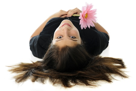 A beautiful preteen laying on her back, looking up over hear head at the viewer while holding a pink flower   On a white background  photo