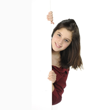 A pretty preteen peeking around a white wall and on a white background Imagens - 14898775
