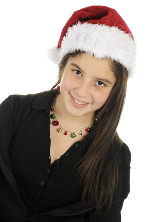 Portrait of a pretty preteen in a Santa hat and colorful jingle bell necklace and earrings    photo