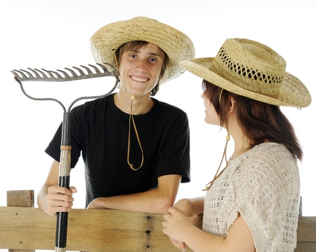 A teen farm boy delighted with the admiration hes receiving from a farm girl.  On a white background. photo