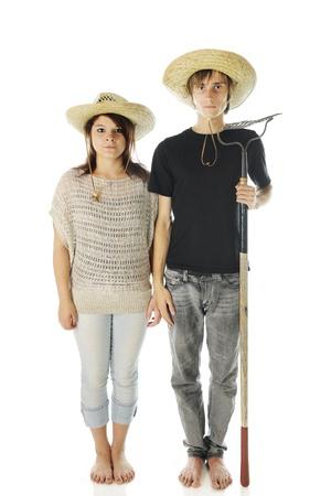 """Ein Teenager """"Landei"""" Paar stand steif und ausdruckslos, barfuß in Jeans und Strohhüte. Der Junge hält eine Harke. Auf einem weißen Hintergrund. Standard-Bild - 14932494"""