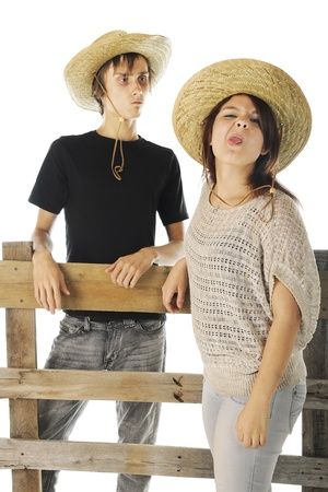 disapprove: A teen farm girl making a nasty face at the viewer while her boyfriend looks on disapprovingly from behind a rail fence.  On a white background. Stock Photo