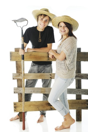 A happy teen couple, barefoot and wearing farm hats standing on either side of an old rail fence.  On a white background.