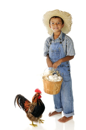 An adorable farm boy with the basket of eggs hes collected. On a white background.