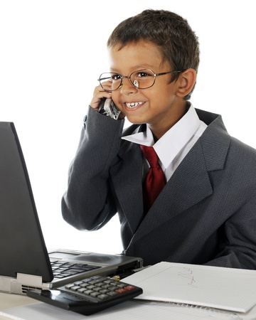 white work: A young elementary boy delightedly talking on the phone behind his computer while wearing his dads business suit.  On a white background. Stock Photo