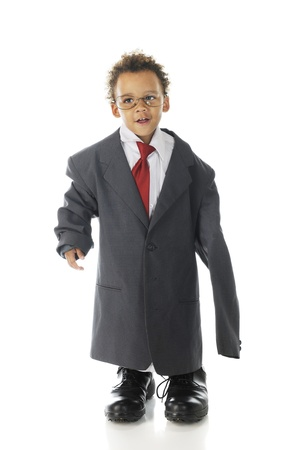 An adorable tot happily dressed in an oversized suit jacket, shirt and tie with his daddy's dress shoes. On a white background.
