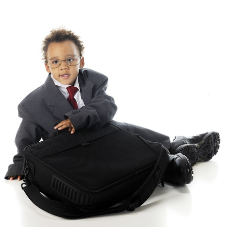 An adorable preschooler in an oversized business suit and his dad's dress shoes, getting ready to open his computer.  On a white background. Stock Photo - 15041387