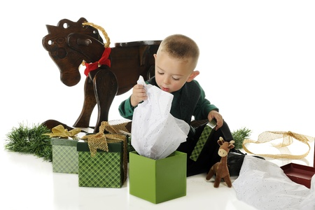 An adorable preschooler lifting the tissue paper, wondering what's inside his Christmas gift box.  On a white background. Stock Photo - 15041393