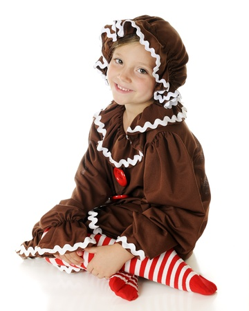 An adorable young elementary gingerbread girl,  happily sitting on the floor.