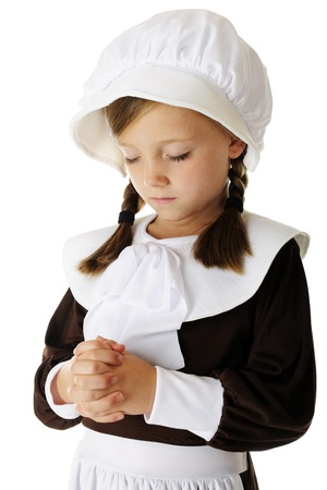 thankfulness: Closeup of a pretty young elementary pilgrim girl in prayer.  On a white background.