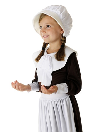 """An adorable young """"pilgrim"""" girl looking upwards with upturned palms in giving thanks to God. On a white background."""