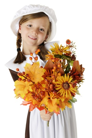 """A beautiful elementary """"pilgrim"""" girl happily holding out a bouquet of autumn flowers, leaves and berries for the viewer. On a white background."""