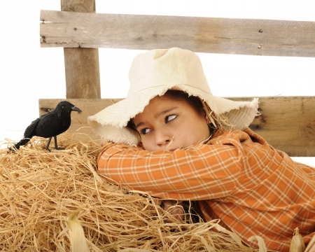 A pretty teen  scarecrow  waking up to find a big old crow perched by her head