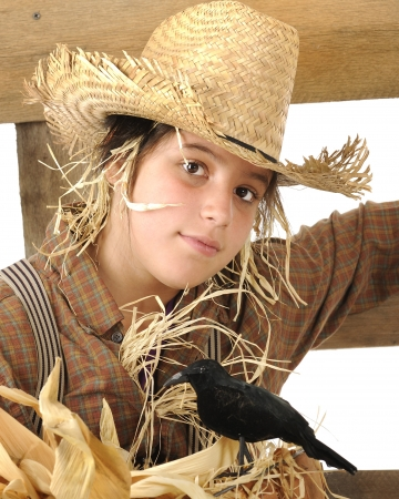 Close-up portrait of a preteen scarecrow   A big black bird is perched on dried corn leaves in the foreground  photo