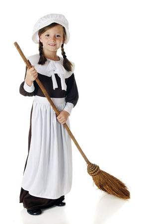 An adorable young pilgrim girl sweeping with an old-style broom   On a white background Stock Photo - 15041412