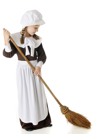 A beautiful young pilgrim girl sweeping   On a white background  Stock Photo - 15041415