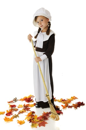 An adorable elementary-aged Pilgrim girl raking leaves   On a white background