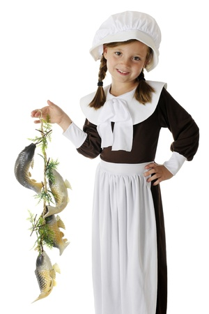 A beautiful, elementary Pilgrim girl happily displaying the colony Stock Photo - 15041409