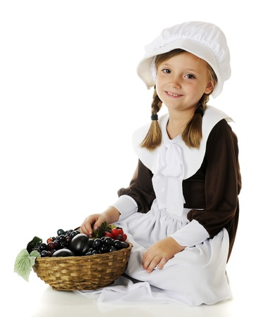 A beautiful elementary Pilgrim girl sitting with a basketful of fruit   On a white background