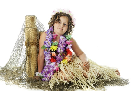 leis: An elementary girl in flower leis and a grass skirt resting against fish-net covered posts.  On a white background.