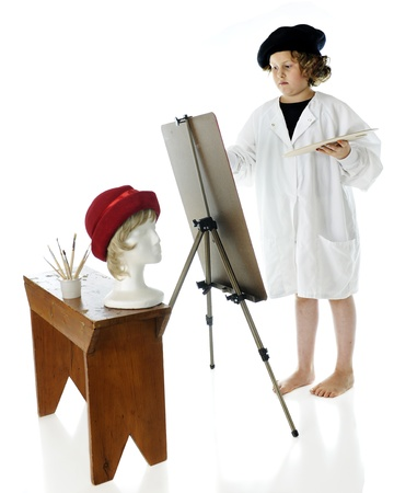 An elementary-aged artist, barefoot while wearing a French beret and white smock, painting a womans head, a model of which is on a bench before her.  On a white background. photo