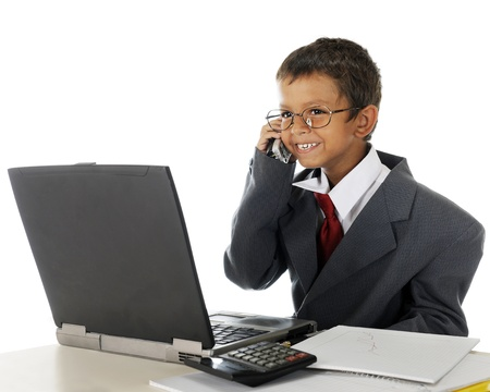 A young elementary boy delightedly talking on the phone behind his computer while wearing his dad's business suit.  On a white background. Stock Photo - 15171805