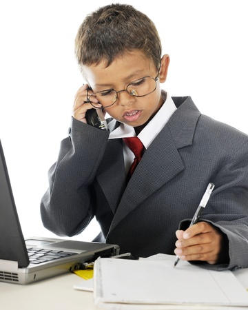 A young elementary businessman in his dads suit.  Hes serious in taking ordersnotes over the phone behind his laptop.  On a white background. photo