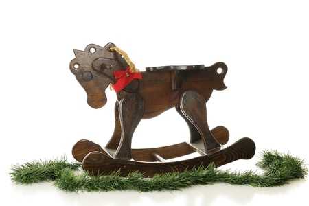 A wooden rocking horse with a red bow and surrounded by Christmas garland.  On a white background.  Stock Photo