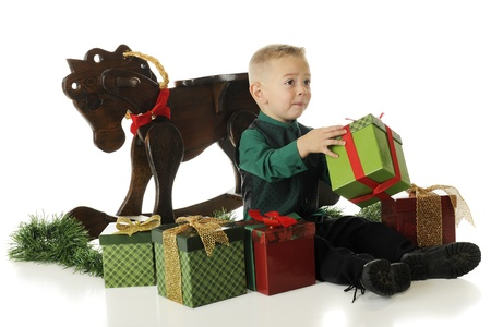 pleading: A young preschooler dressed up for Christmas, pleading for help with opening a gift.  On a white background.