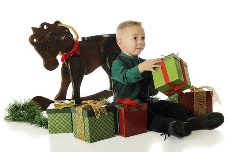 suplicando: Un ni�o en edad preescolar joven vestida para la Navidad, pidiendo ayuda con la apertura de un regalo. En un fondo blanco.