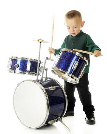cymbol: A young preschooler intently drumming on a child-sized drum set.  On a white background.  (Motion blur on lower drum stick.) Stock Photo