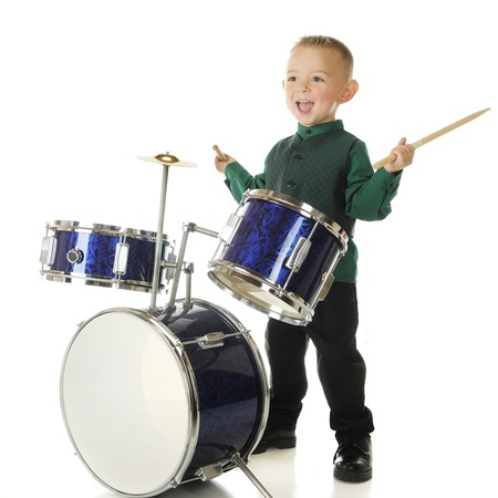 cymbol: An adorable preschooler delighted to be playing the drums.  On a white background.